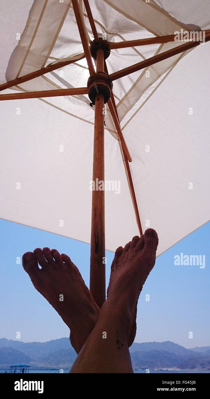 Low Section Of Person Against Sunshade - Stock Image