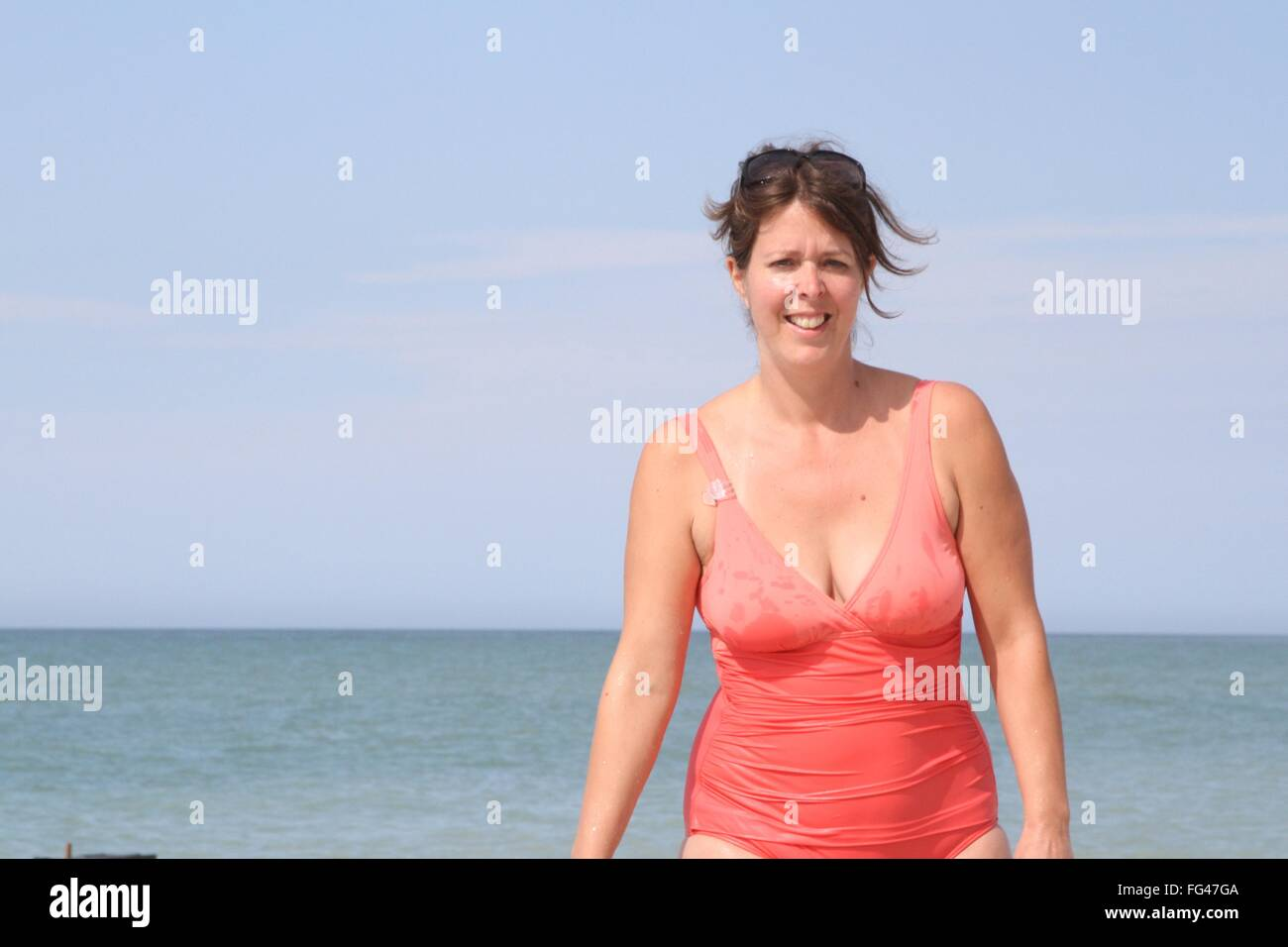 Beautiful and happy young woman in a bathing suit - Stock Image