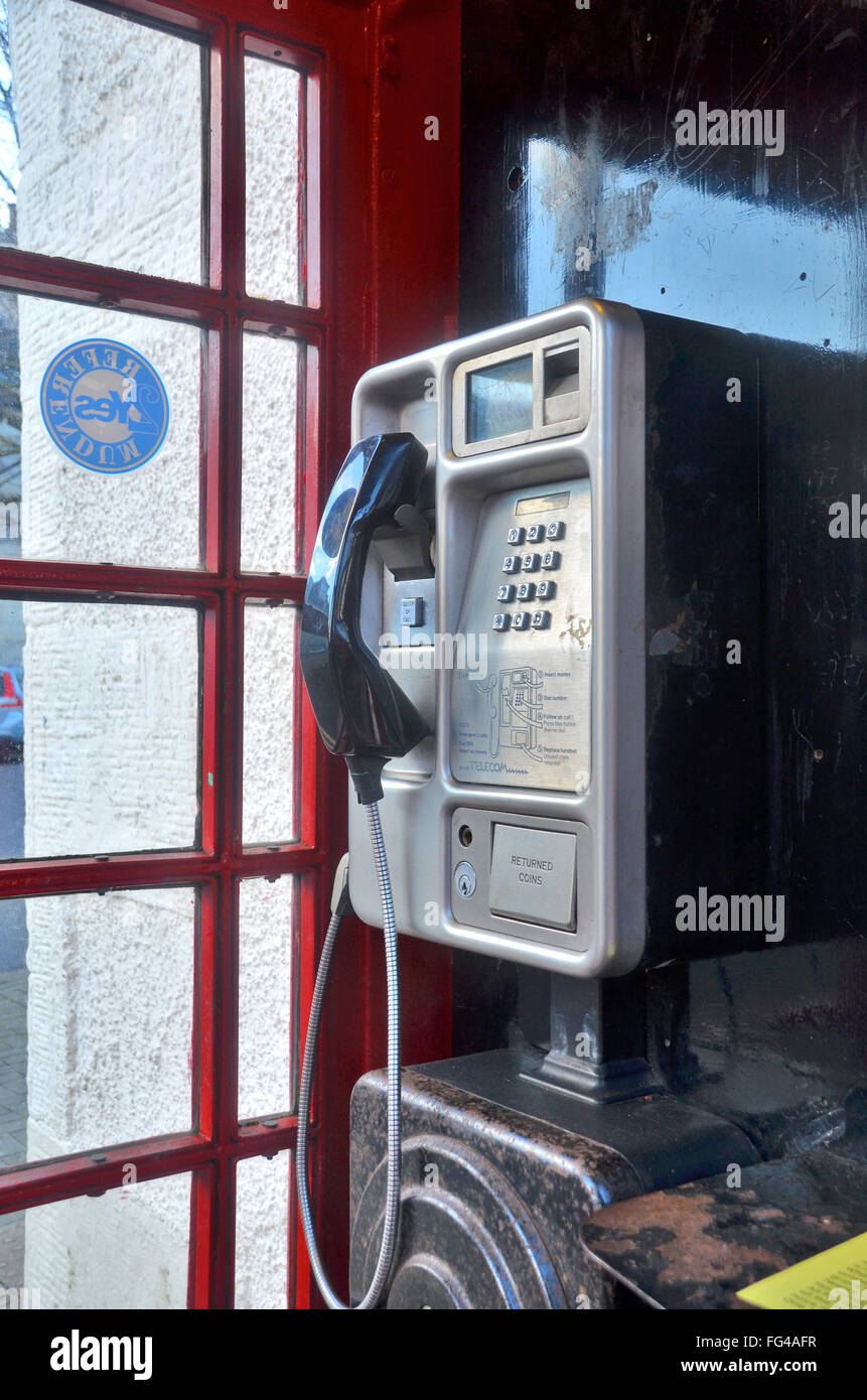 A red UK phone box with a money / coin paying landline telephone. - Stock Image