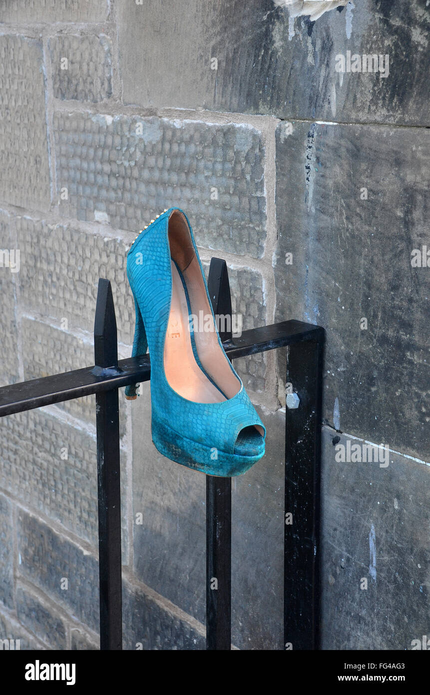 A   woman's blue high heel stiletto party shoe, sitting on a railing after a wild night out. - Stock Image