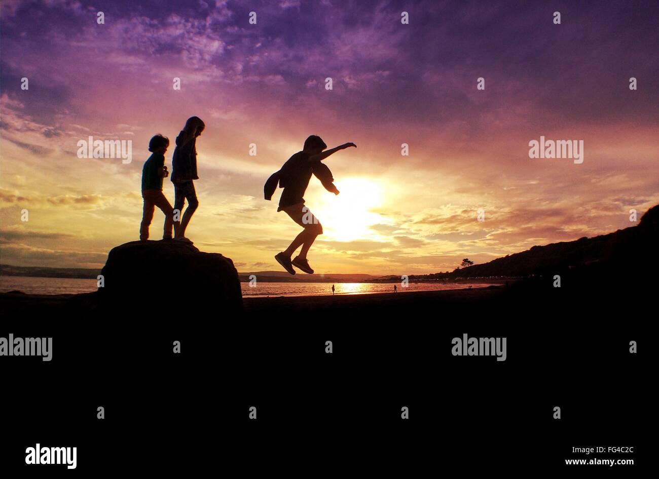 Silhouette Friends Enjoying On Beach Against Orange Sky - Stock Image