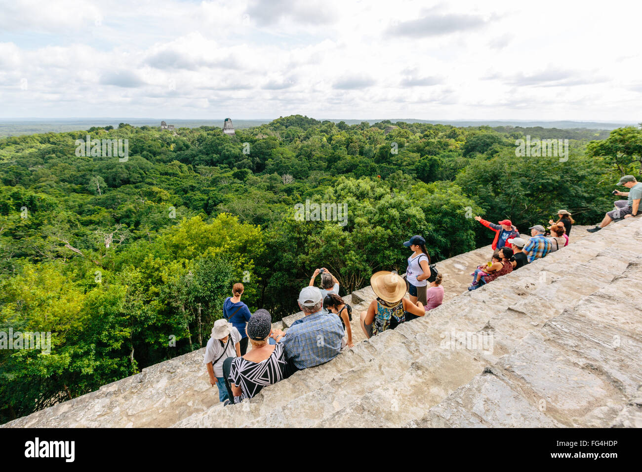 Tourists on top of Temple IV, Temples I, II, III & V rise above the forest canopy Stock Photo