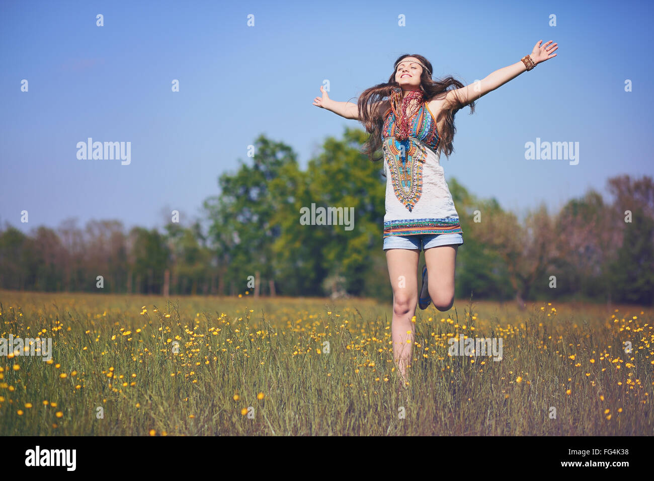 Happy and smiling hippie woman jumps in a summer field . Vintage photo effect Stock Photo