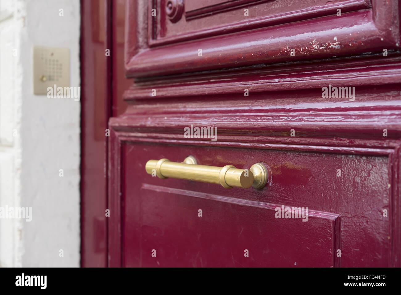 Old Brass Door Handle On Sturdy Old Textured Maroon Red Wooden Door