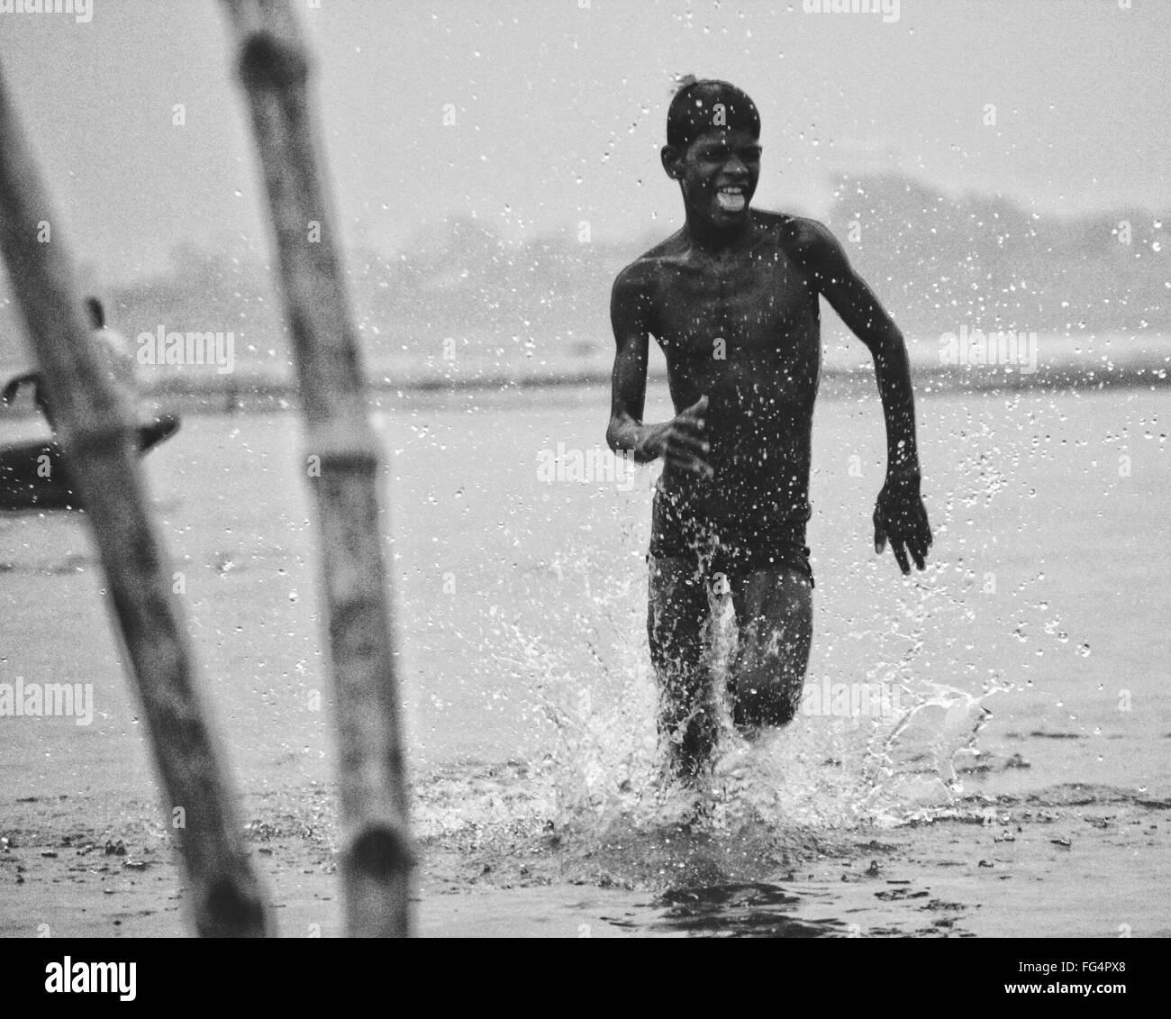 Shirtless Teenage Boy Running In Water At Beach - Stock Image
