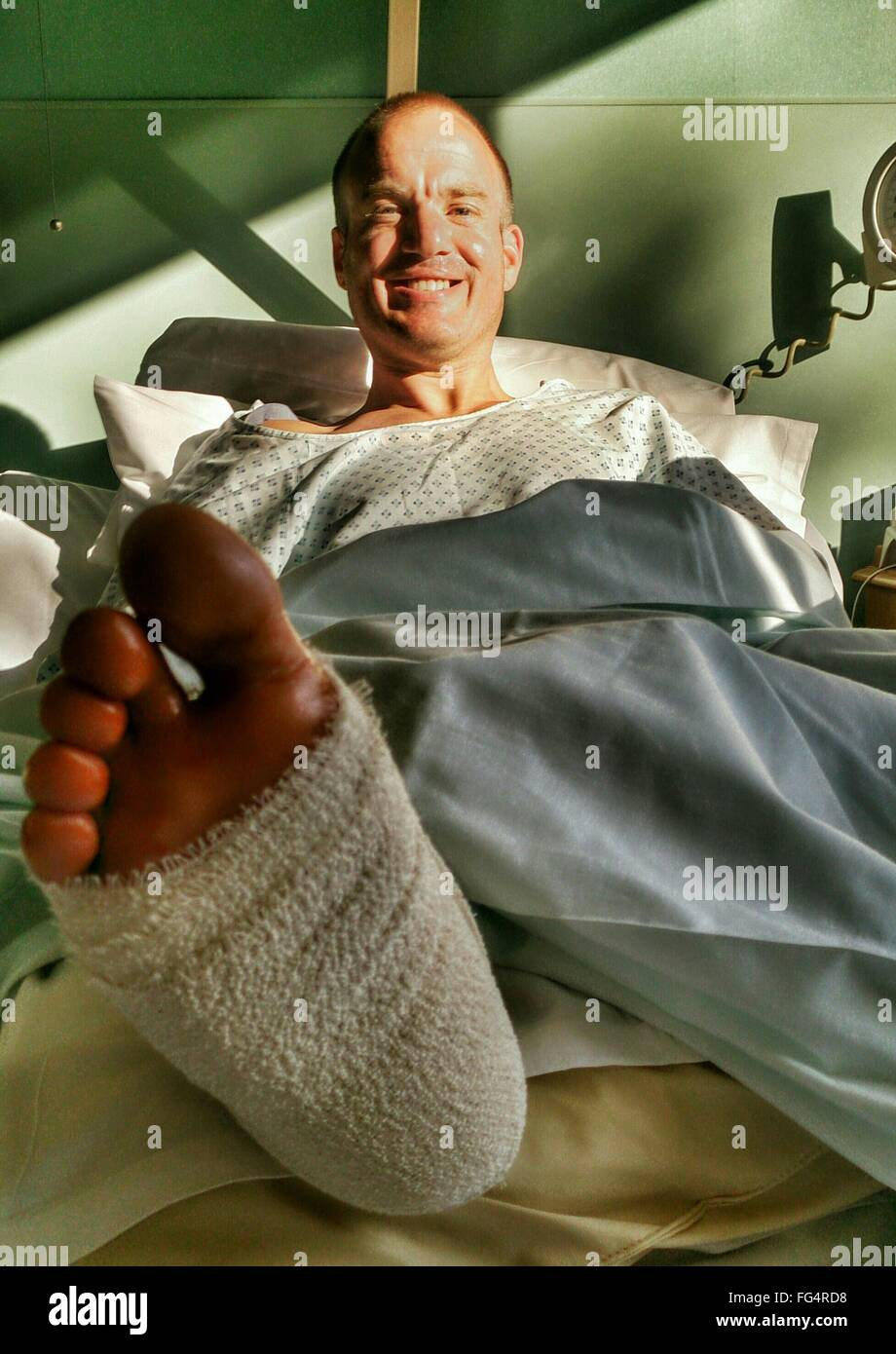 Portrait Of Happy Mid Adult Man With Broken Leg Recovering In Hospital Bed - Stock Image