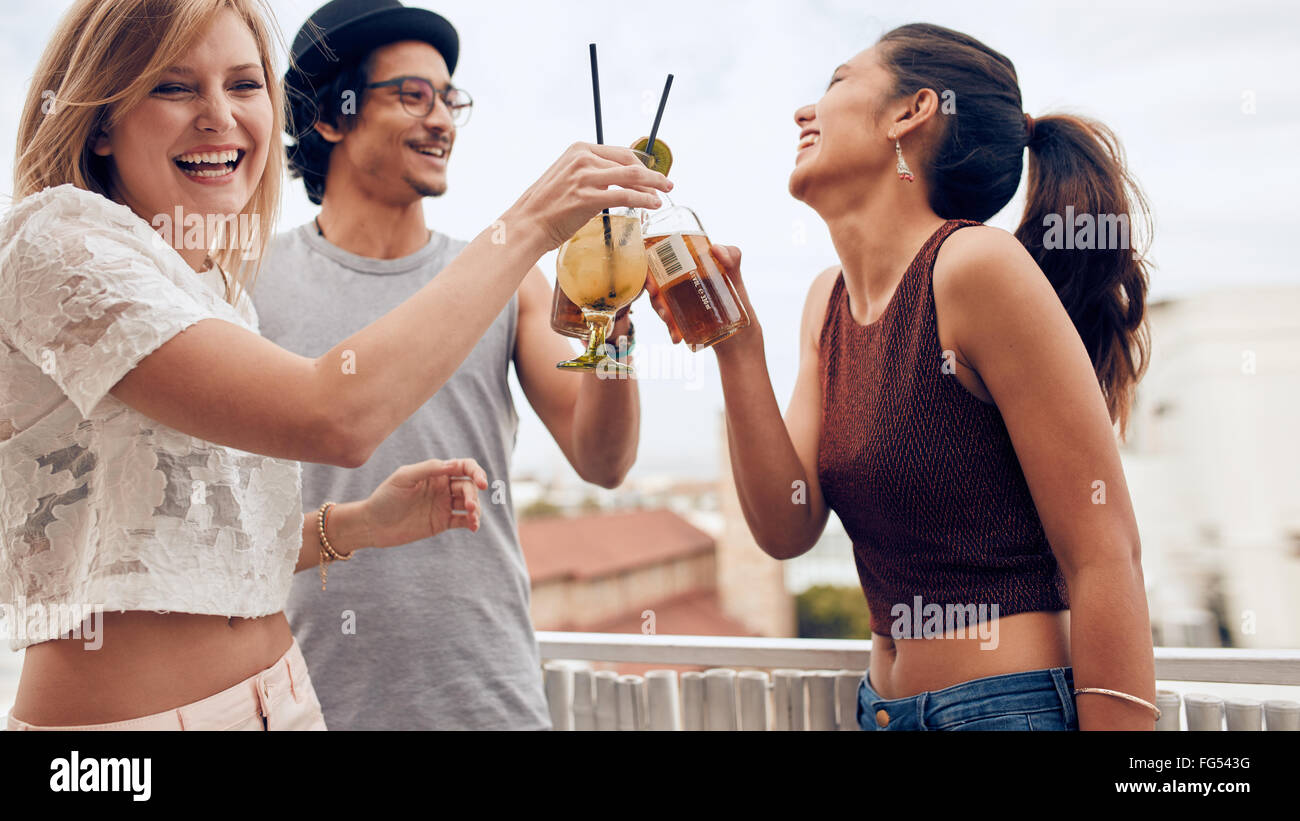 Portrait of young woman toasting cocktail with her friends during a party. Three young friends enjoying in a party. - Stock Image