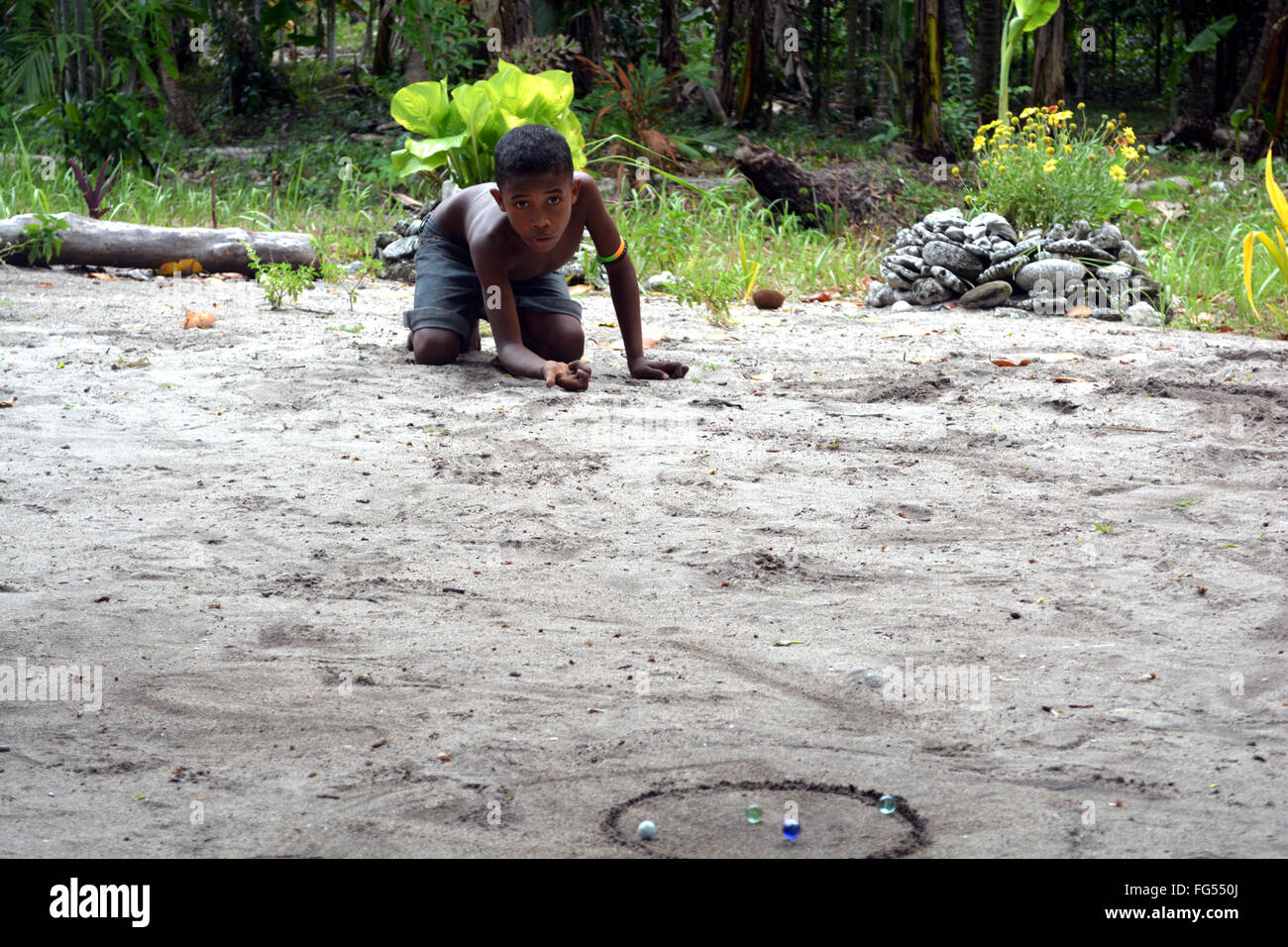 boy playing marbles in PNG - Stock Image