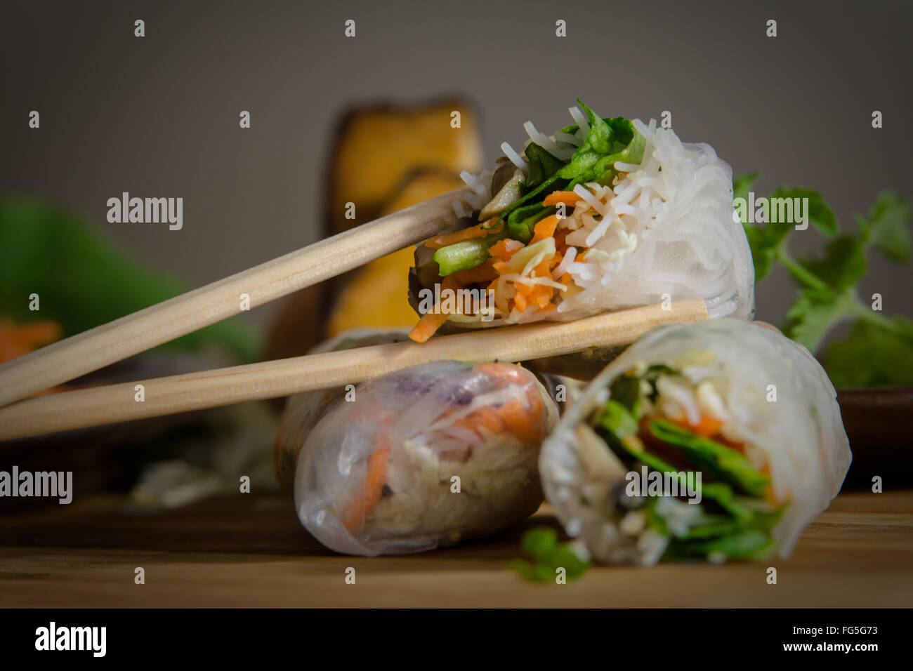 Vietnamese summer rolls surrounded with rice paper and stuffed with various vegetables. Vegetarian food. Asian food. - Stock Image