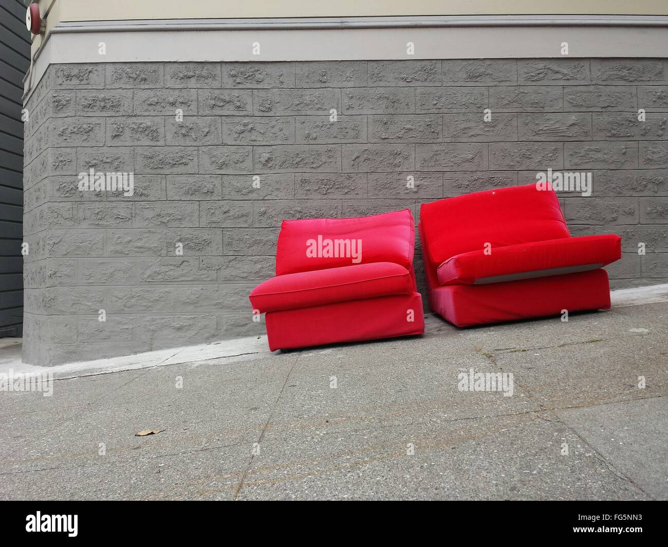 Red Abandoned Couches On Sutter Street Against Wall - Stock Image