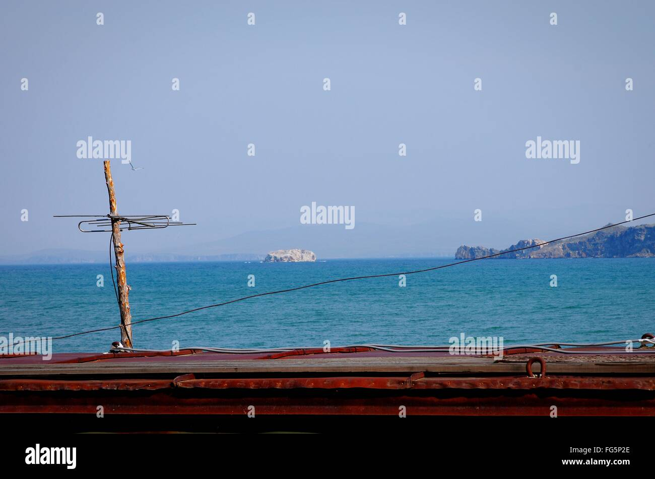Television Aerial On Roof Against Sea - Stock Image