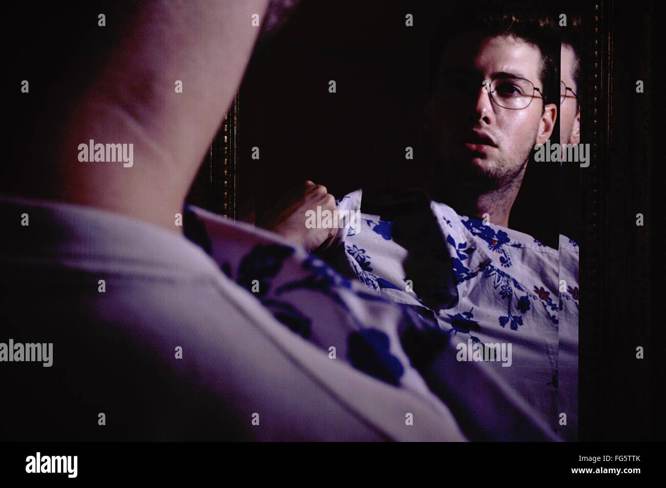 Reflection Of Man Trying Shirt In Mirror - Stock Image