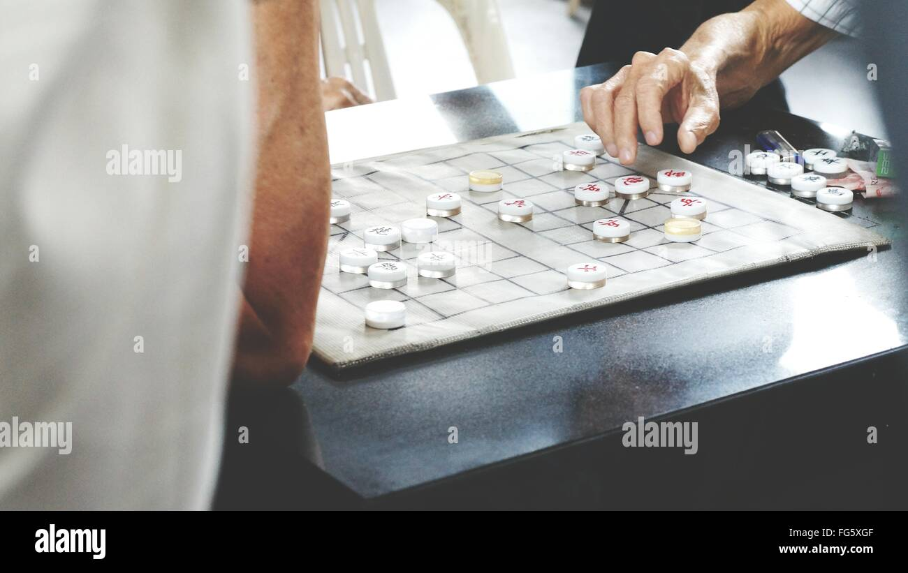 People Playing Checkers On Table Stock Photo