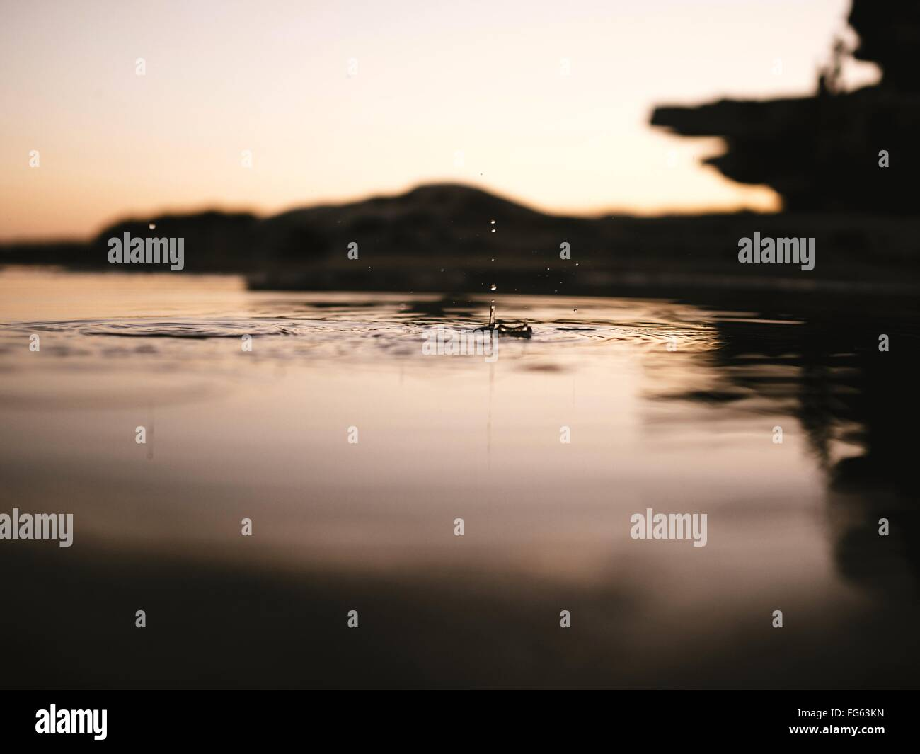 Close-Up Of Drop Falling On Water At Lake Against Sky During Sunset - Stock Image