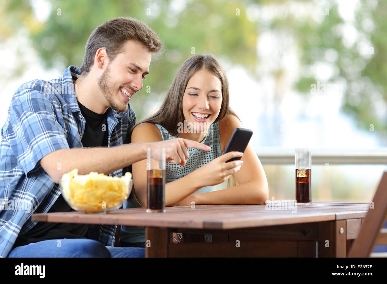 Couple sharing a smart phone sitting on a hotel or home terrace - Stock Image