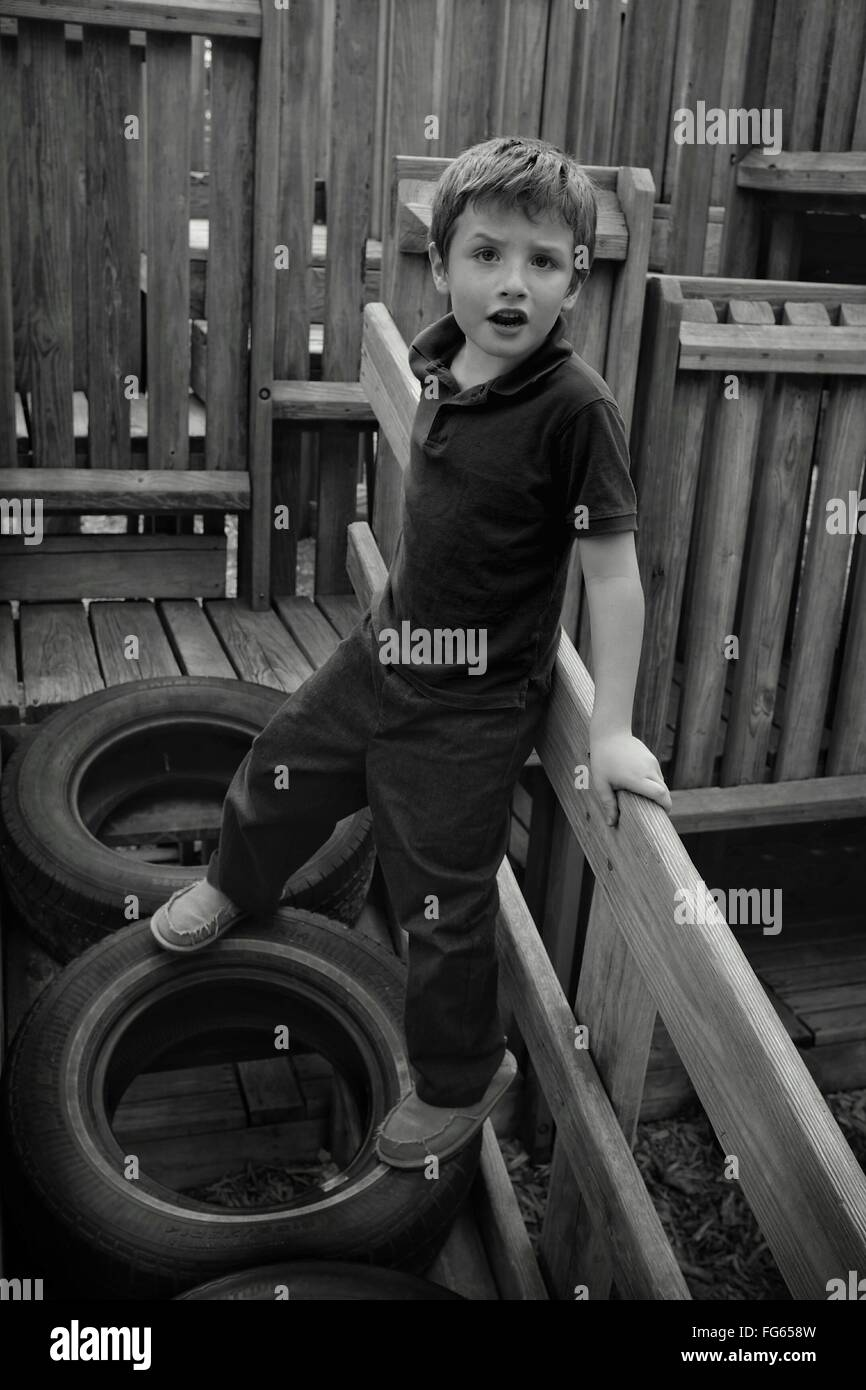 High Angle Portrait Of Boy Standing On Tire At Playground Stock Photo