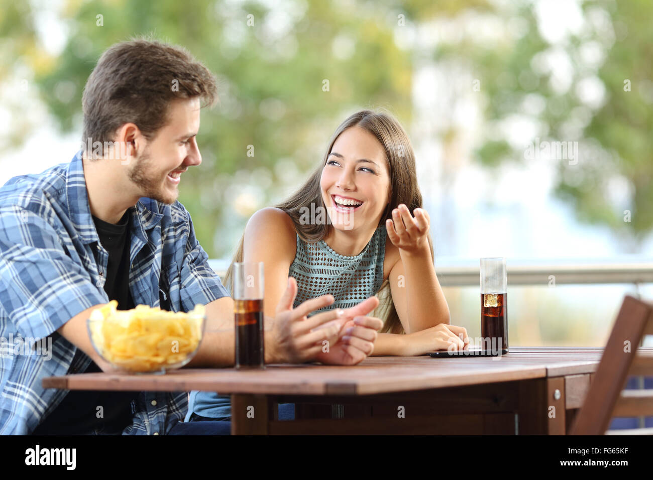 Girl talking with a friend in a terrace with snacks and drinks - Stock Image