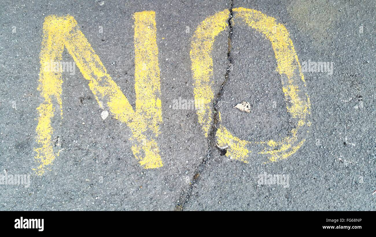 High Angle View Of Yellow No Marking On Cracked Street - Stock Image