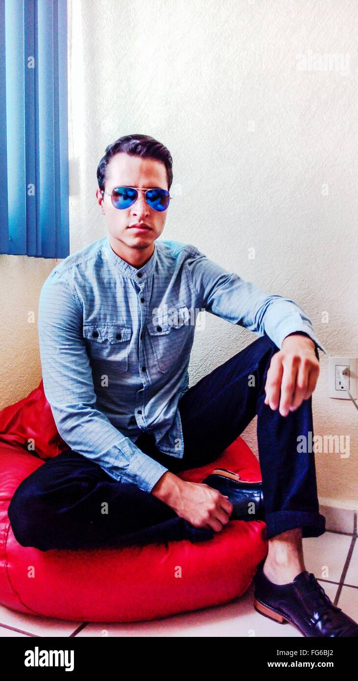 Young Man Wearing Sunglasses Sitting On Bean Bag Against Wall - Stock Image