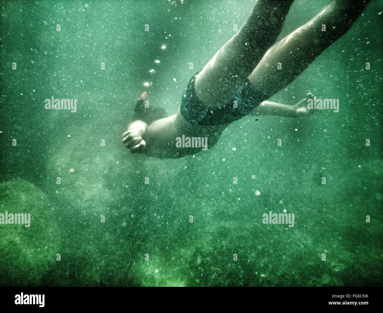 Low Angle View Of Man Swimming Undersea - Stock Image