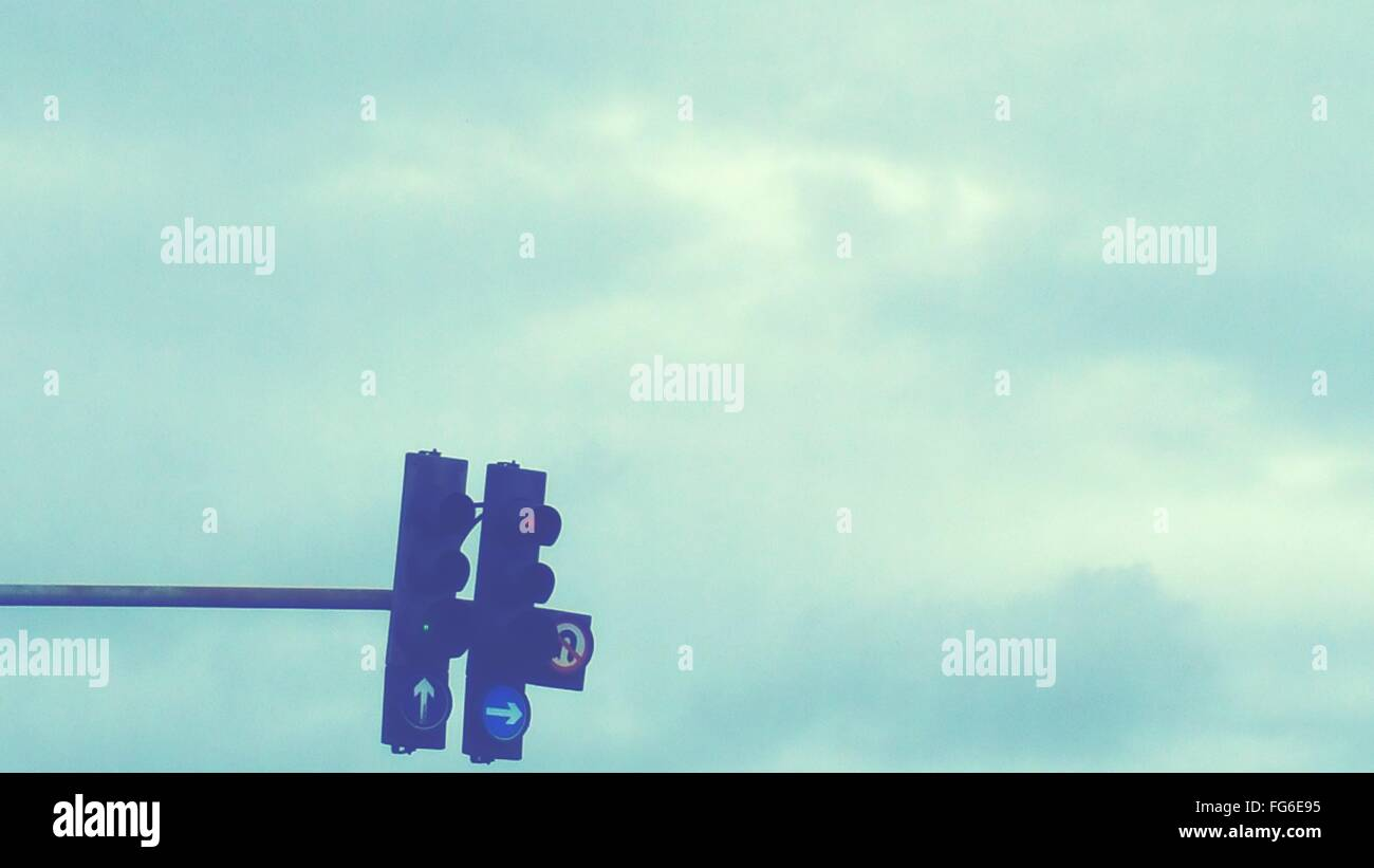 Low Angle View Of Illuminated Road Signal Against Cloudy Sky - Stock Image