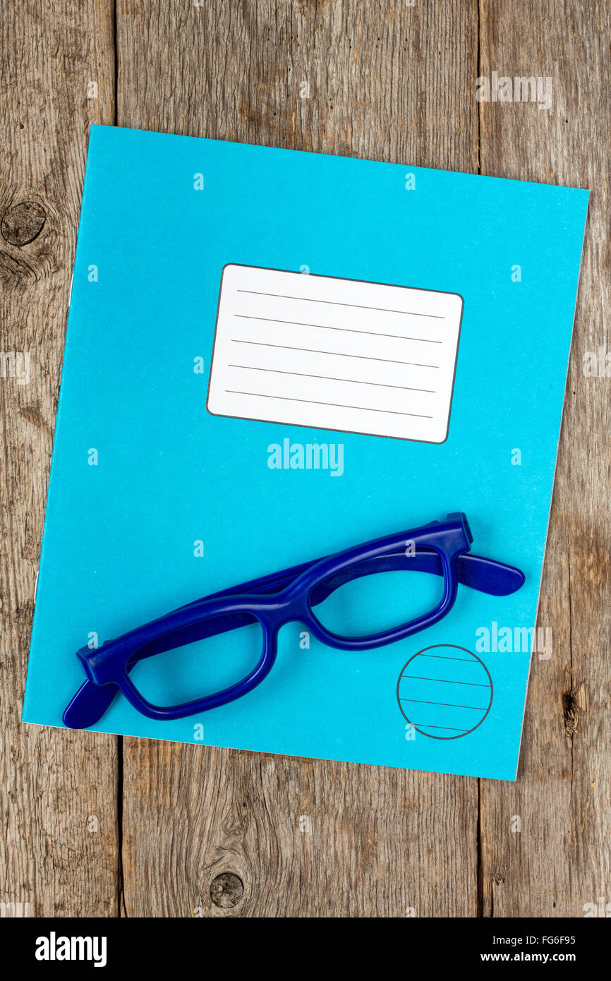 Blue exercise book and glasses on the wooden background - Stock Image