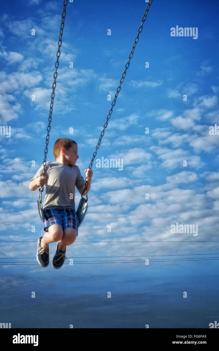 Boy Swinging Against Cloudy Blue Sky - Stock Image