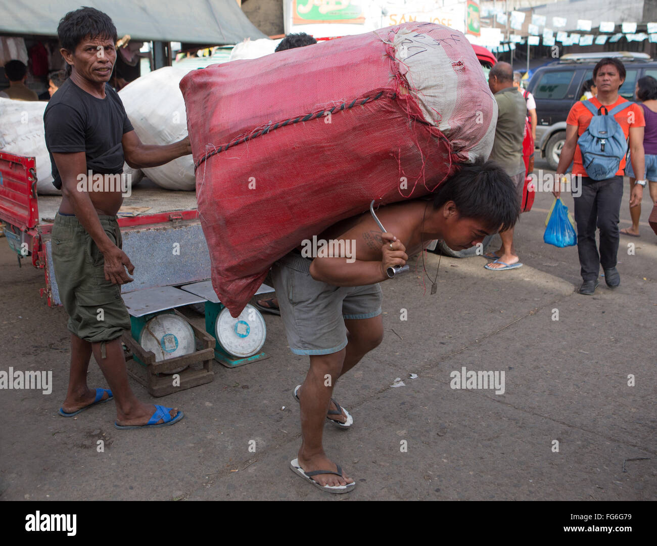 A heavy load being carried by a Filipino man within the Carbon Market located in Downtown Cebu City ,Philippines - Stock Image