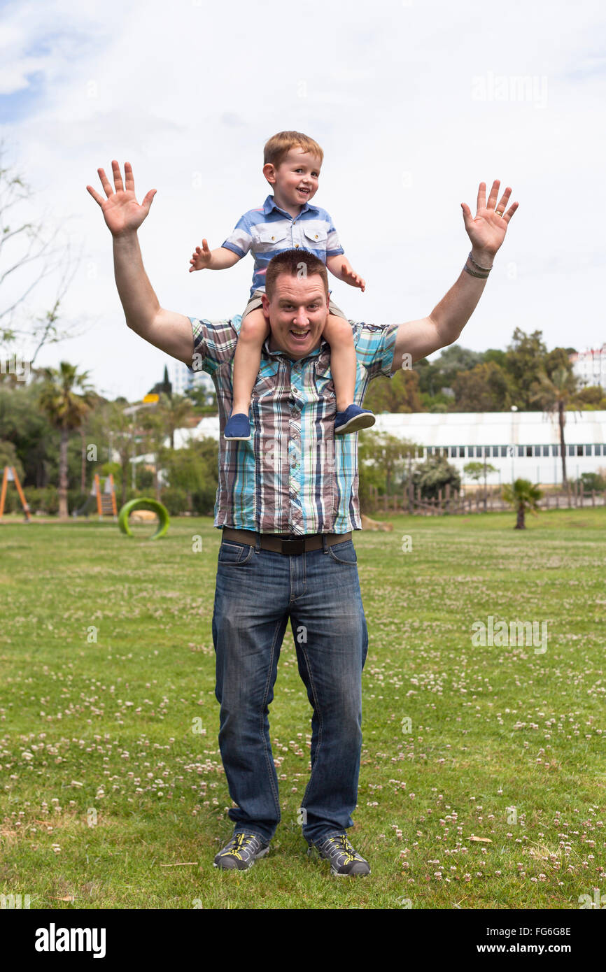 Happy daddy and his son having fun in the park outdoors. Happiness, fatherhood and childhood concept. Stock Photo