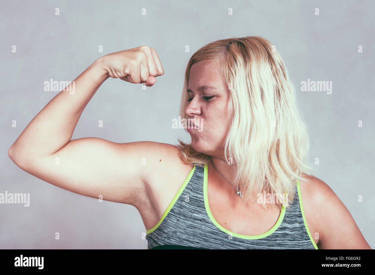 Strong confident muscular woman flexing her muscles. Young blond sporty female showing arm and biceps. - Stock Image