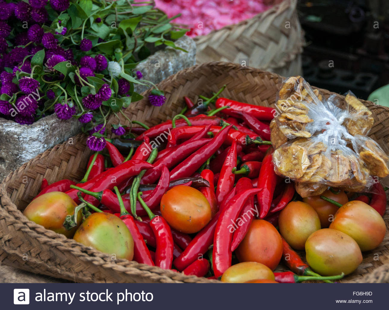 A basket of red chilies and tomatoes next to flowers at the produce market in Ubud, Bali - Stock Image