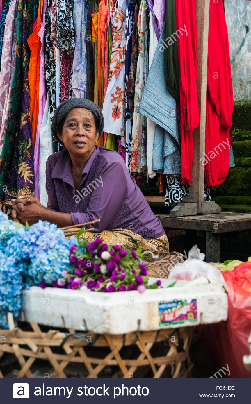 A seller leans over at her stall in the produce market in Ubud, Bali. She is surrounded by color from flowers and - Stock Image