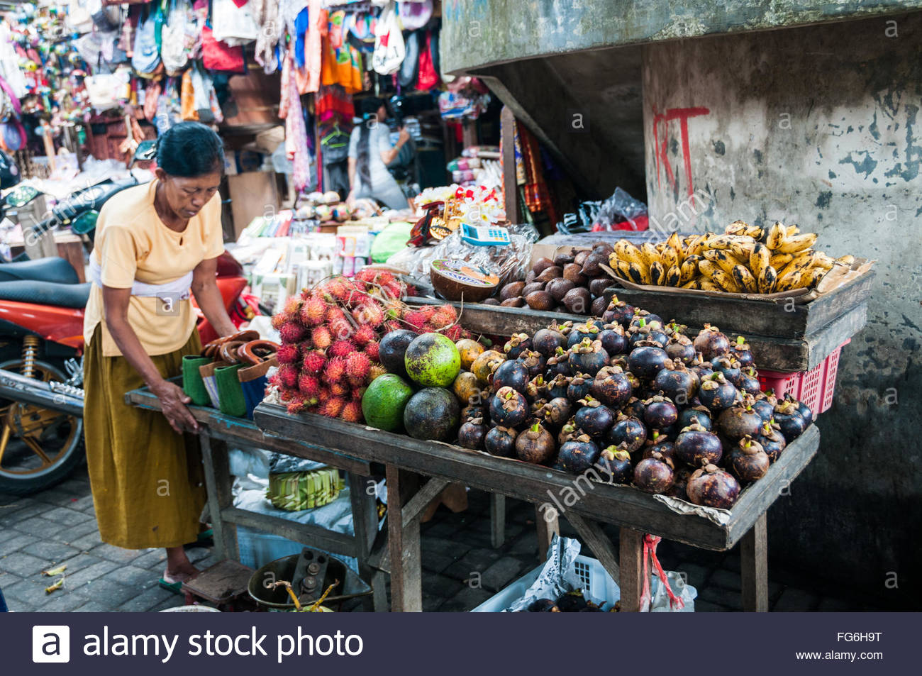 A fruit seller with her table of fruit and some bags at the Ubud market, Bali - Stock Image