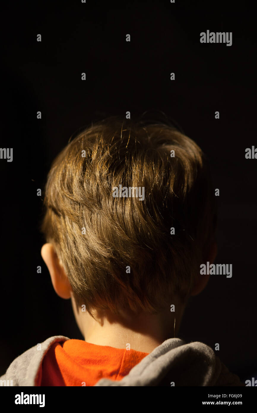 Rear View Of Boy With Brown Hair Against Black Background - Stock Image