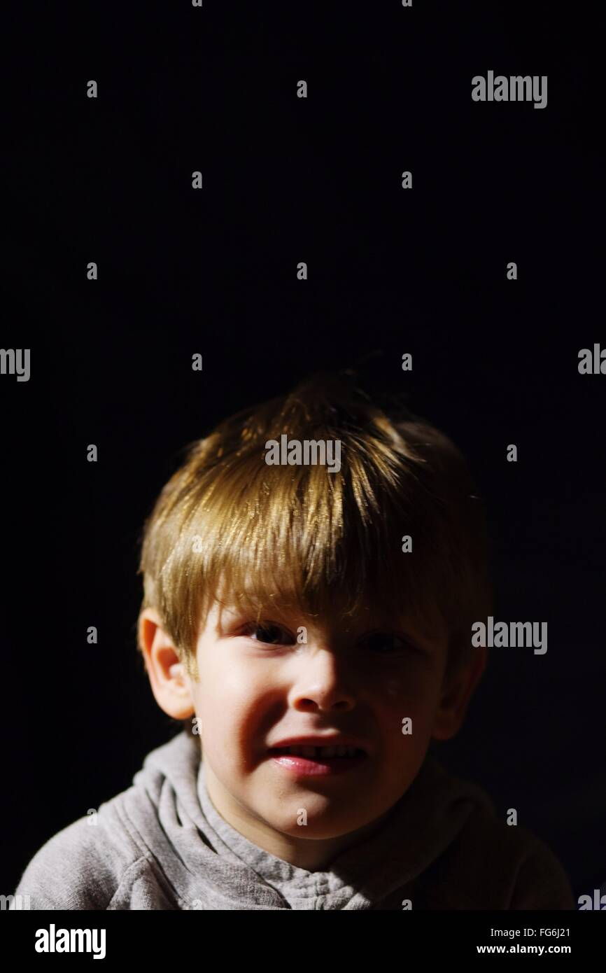Portrait Of Smiling Boy Against Black Background - Stock Image