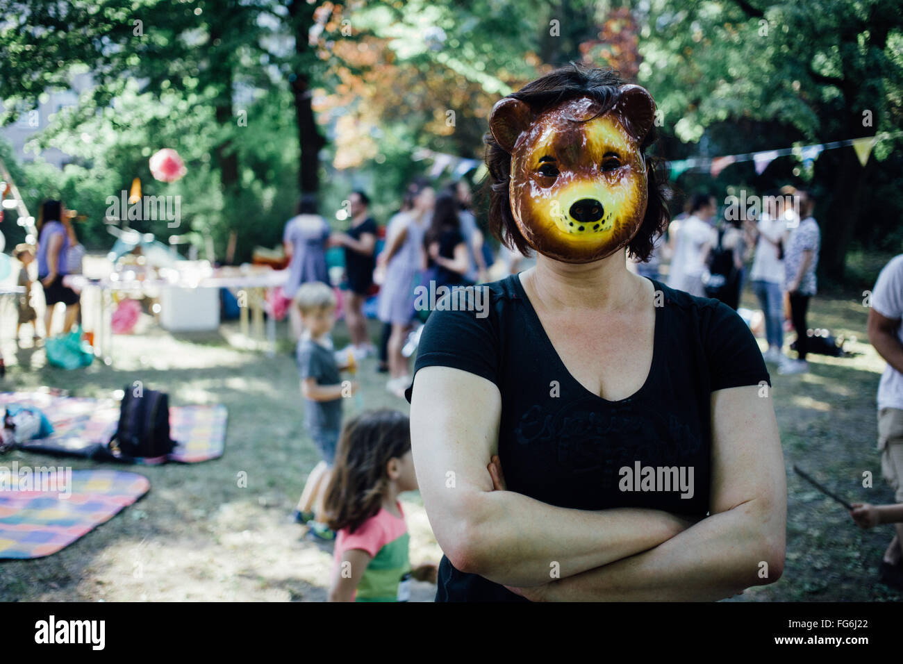 Portrait Of Woman Wearing Tiger Mask In Park - Stock Image