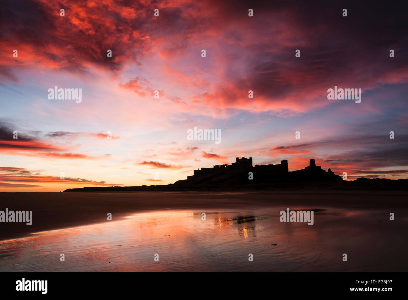 Bamburgh Castle viewed from Bamburgh Beach at sunrise, Bamburgh, Northumberland, England, United Kingdom - Stock Image
