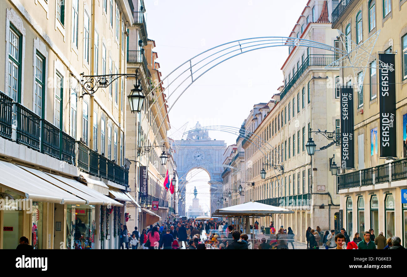 People on Augusta street with the Triumphal Arch, the famous tourist attraction in Lisbon. - Stock Image