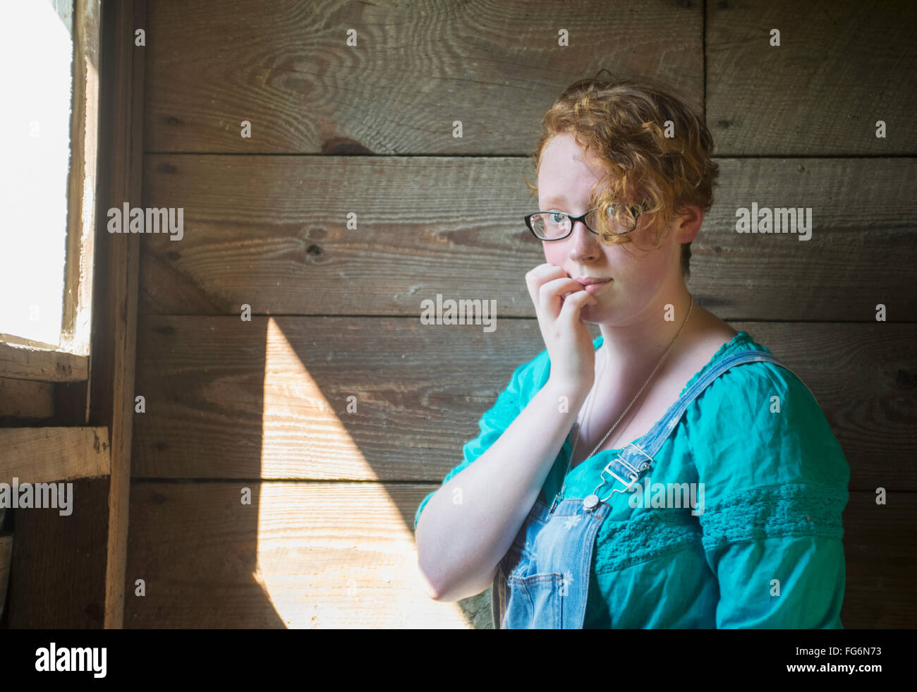 Portrait of a girl with curly red hair and eyeglasses standing against an old, wooden barn wall; Pittsboro, North - Stock Image