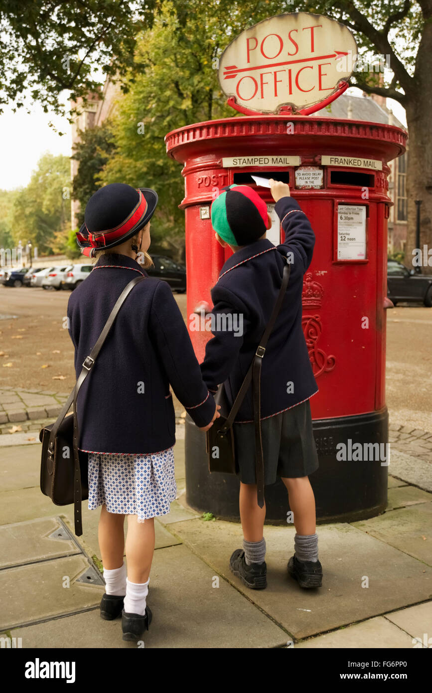 Brother and sister holding hands posting letter; London, England - Stock Image