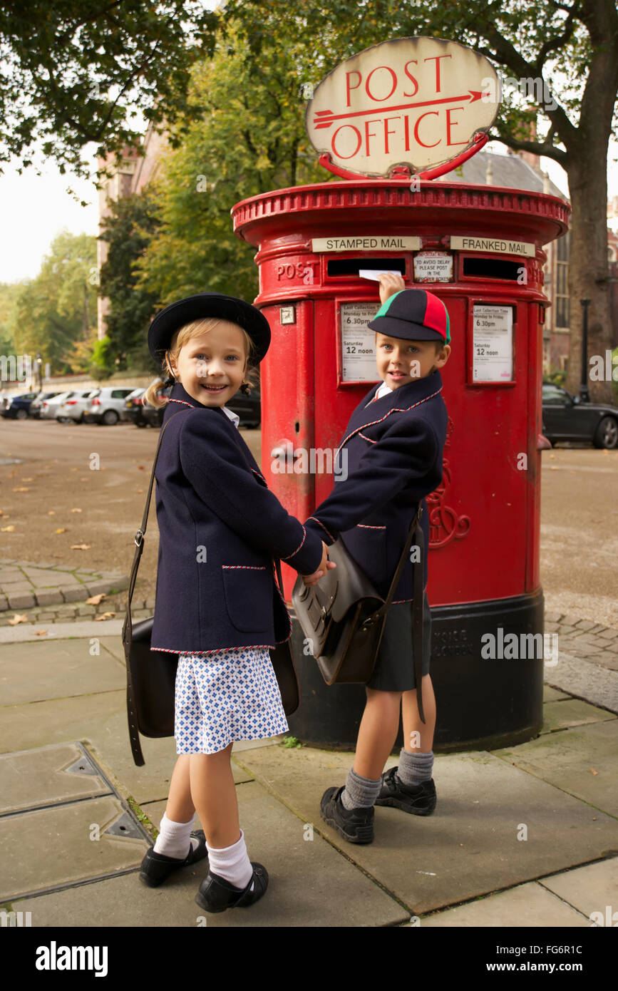 Schoolboy and sister smiling while posting letter; London, England - Stock Image