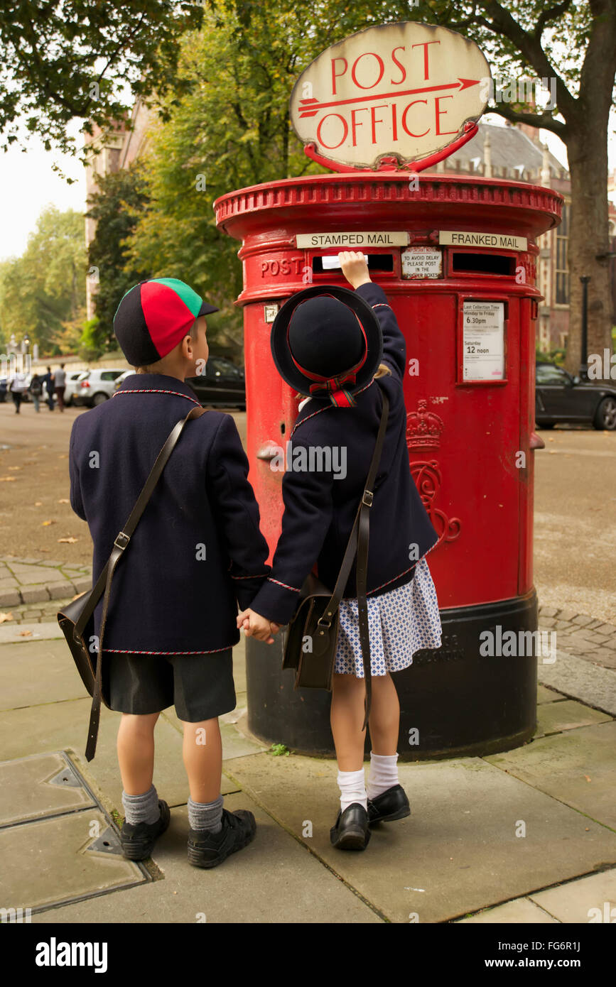 Sister and brother holding hands posting letter; London, England - Stock Image