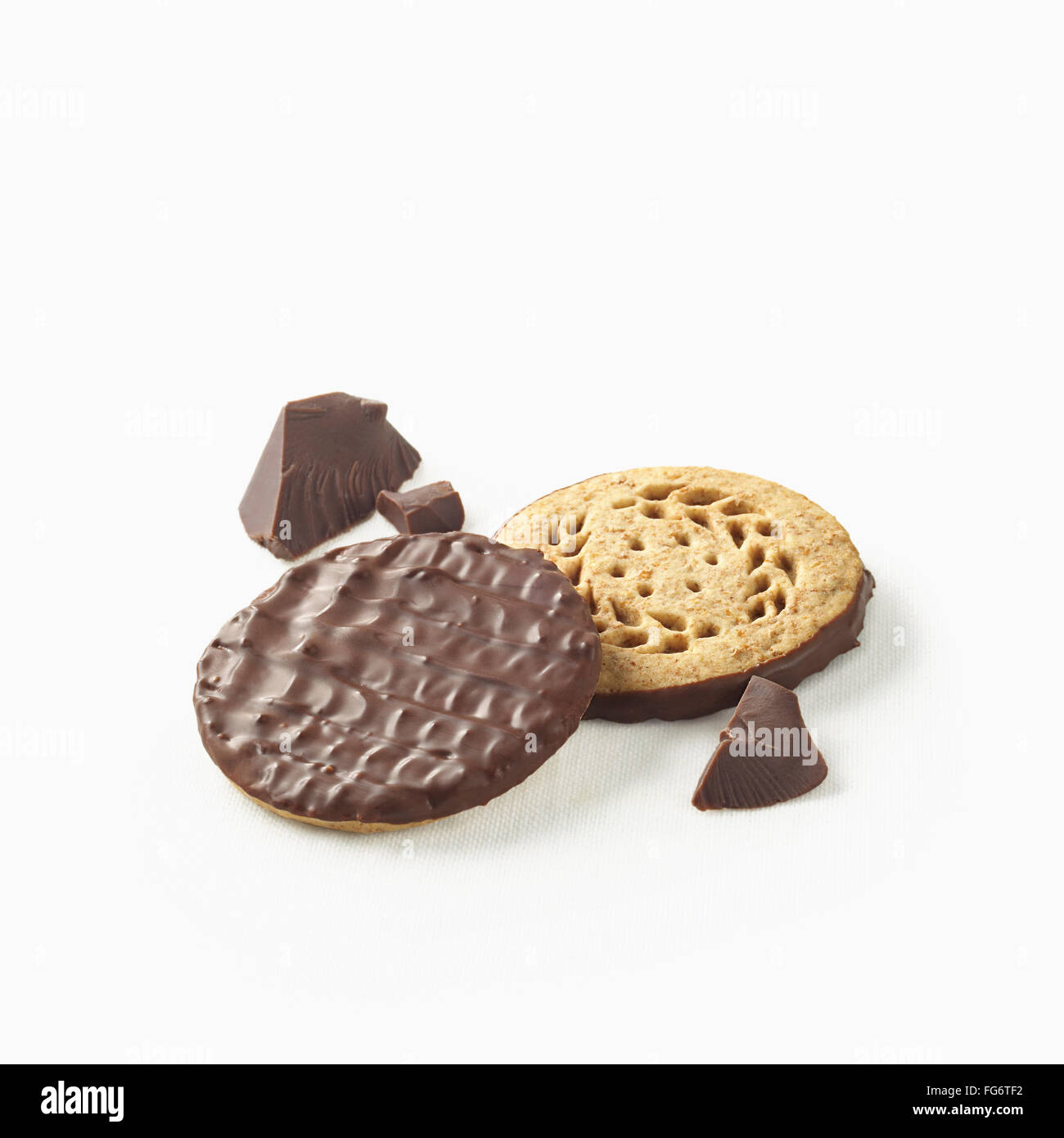 Chocolate covered cookies with pieces of chocolate on a white background; Toronto, Ontario, Canada Stock Photo