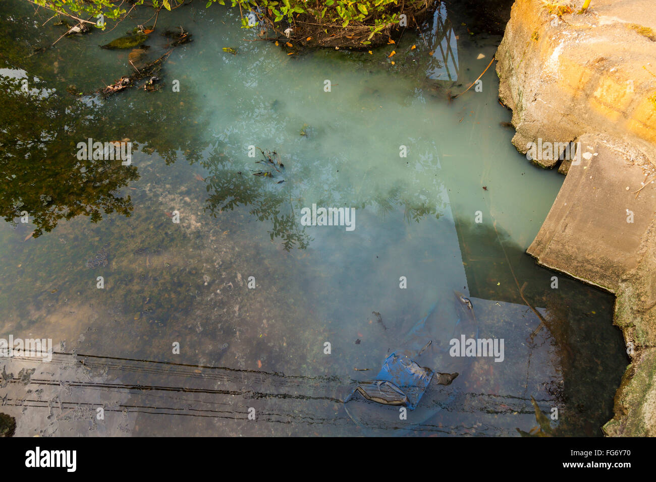 Untreated water makes its way to a stream from a pipe in Quepos, Puntarenas Province, Costa Rica. - Stock Image