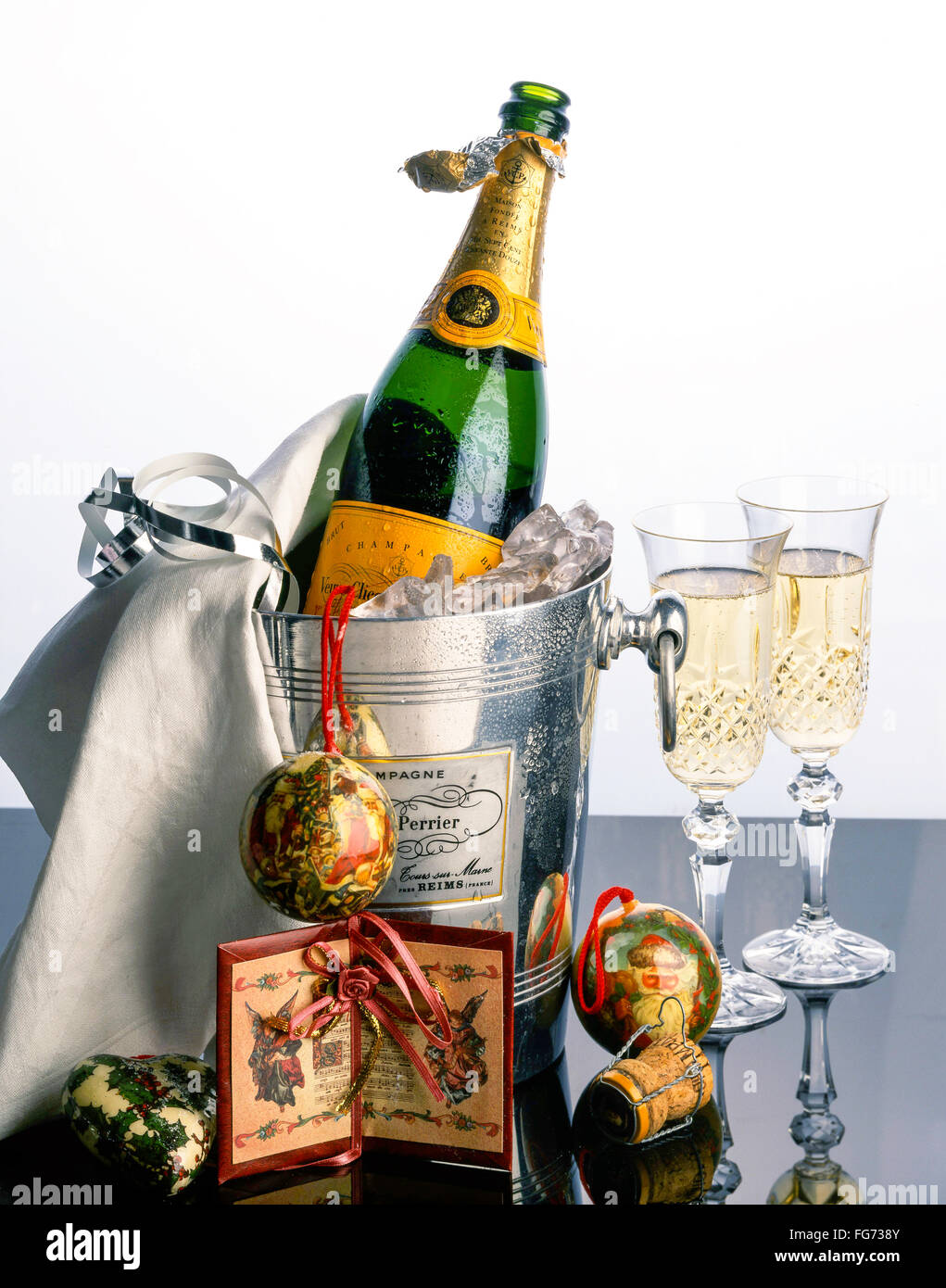 Veuve Clicquot champagne in ice-bucket with Christmas decorations and crystal glasses, London, England, United Kingdom - Stock Image