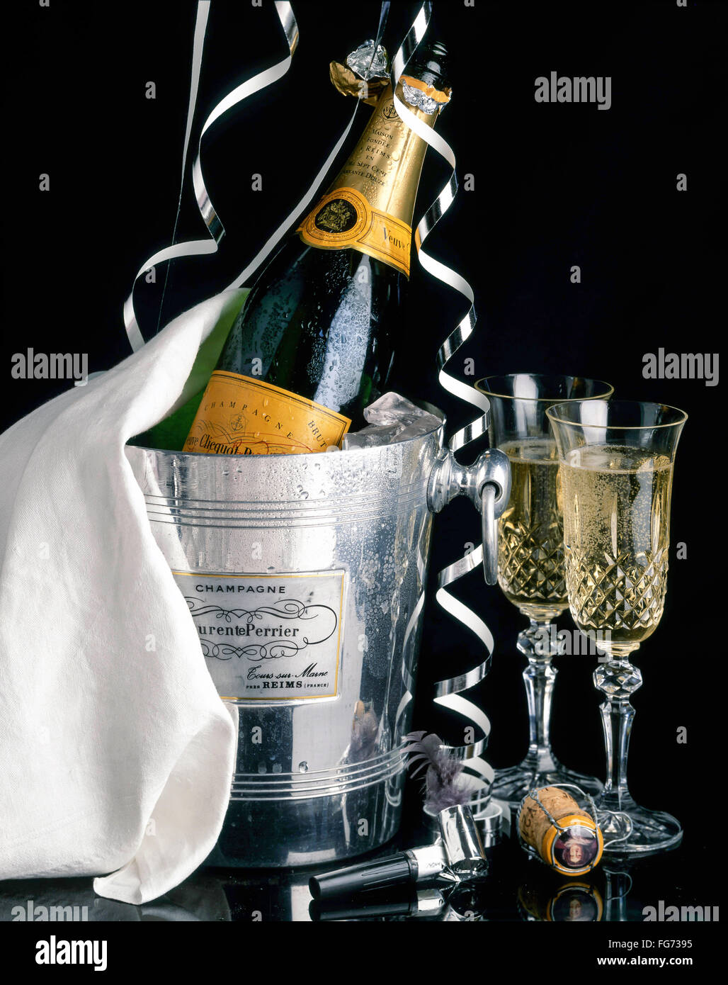 Veuve Clicquot champagne in ice-bucket with streamers and crystal glasses, London, England, United Kingdom - Stock Image