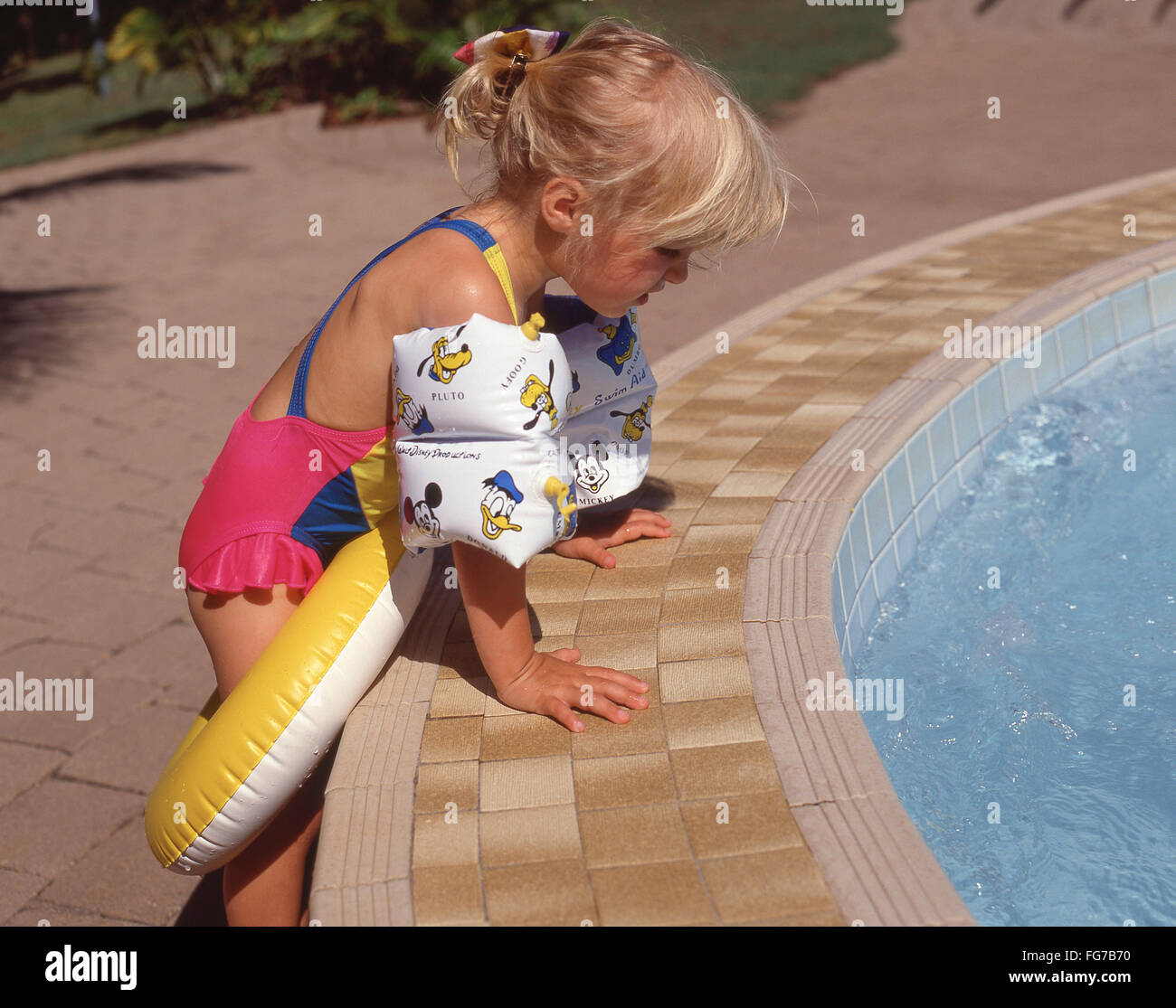 Young blonde girl by swimming pool, Mahón, Menorca, Balearic Islands, Spain - Stock Image