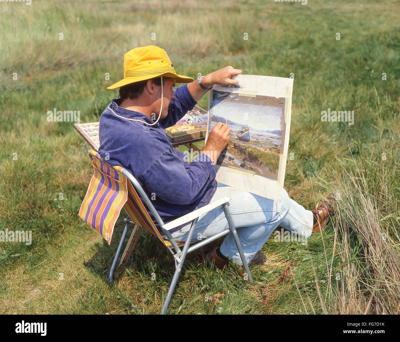 Male artist painting landscape near Aldeburgh, Suffolk, England, United Kingdom Stock Photo