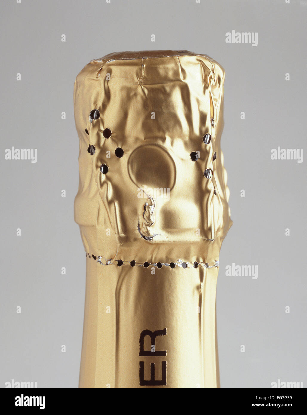 Top of champagne bottle with golden foil in studio setting, London, England, United Kingdom - Stock Image
