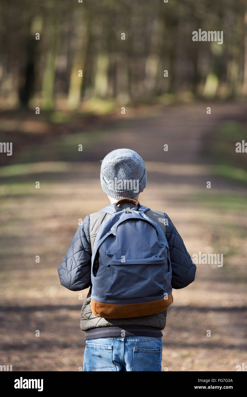 A boy with a rucksack walking in the woods - Stock Image